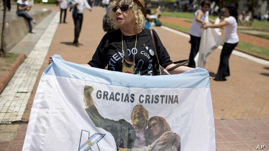 "A government supporter holds an Argentine flag that reads in Spanish ""Thanks Cristina"" featuring an image of late President Nestor Kirchner and his wife, current President Cristina Fernandez in Buenos Aires, Argentina, on Dec. 9, 2015."