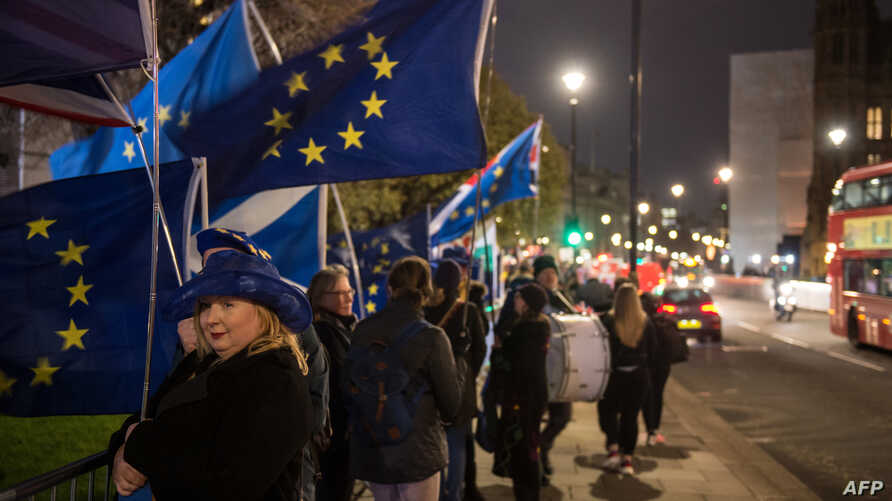 Anti-Brexit supporters hold European Union flags as they demonstrate outside the Houses of Parliament on Jan. 14, 2019.