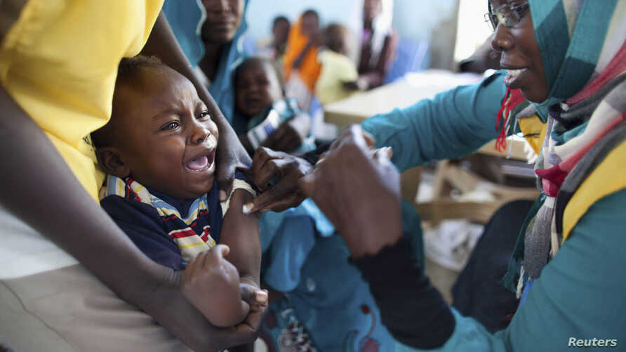 FILE - A child receives a meningitis vaccination at the community center in Al Neem camp for Internally Displaced People in El Daein, East Darfur, Oct. 8, 2012.