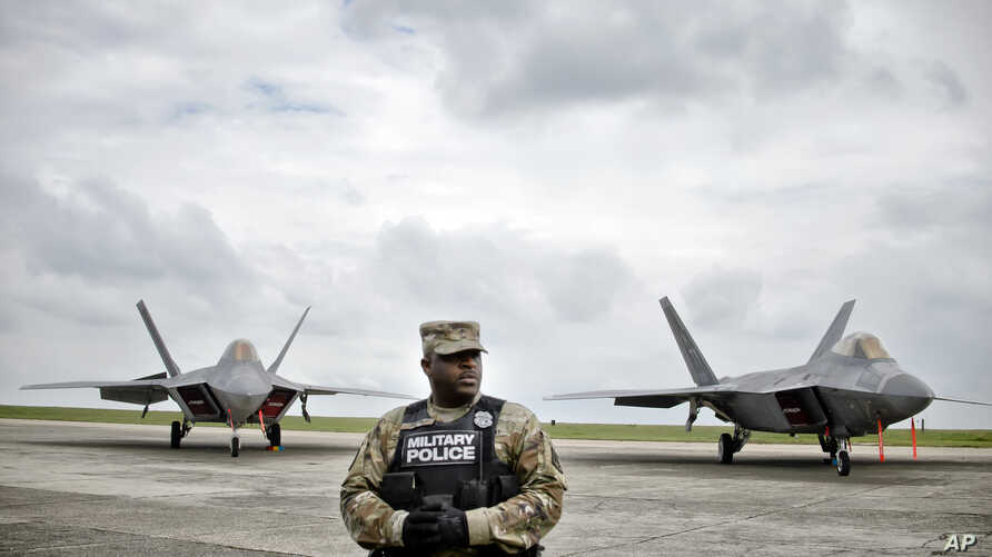 A member of the U.S. military police stands in front of U.S. Air Force F-22 Raptor fighter jets that were flown April 25, 2016, to the Mihail Kogalniceanu air base, near the Black Sea port of Constanta in southeast Romania, as a show of support to de