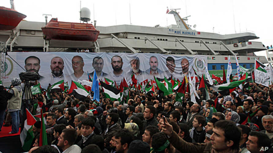 People, holding Turkish and Palestinian flags, cheer as the Mavi Marmara ship, in the background, the lead boat of a flotilla headed to the Gaza Strip which was stormed by Israeli naval commandos in a predawn confrontation in the Mediterranean May 31