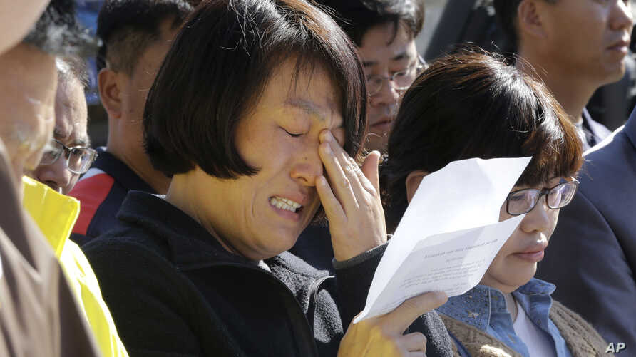 An unidentified family member of passengers aboard the sunken ferry Sewol caries as she demands maximum punishment to be sentenced on the crew members of the ferry during their trial at Gwangju District Court in Gwangju, South Korea, Oct. 27, 2014.