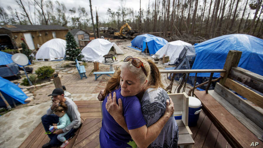 """Diahnn """"Shelly"""" Summers, right, embraces Lori Hogan, who is currently living in a tent in Summers' backyard months after Hurricane Michael hit in Youngstown, Fla, Wednesday, Jan. 23, 2019."""