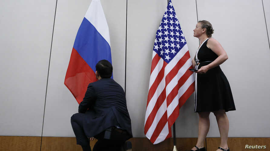 FILE - Staffers install U.S. and Russian flags as part of a bilateral meeting, Aug. 26, 2016. Theoretically, U.S. President Donald Trump and Russian President Vladimir Putin would have an opportunity to meet Friday in Vietnam but it's not clear wheth...