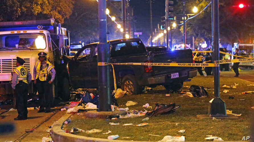 Police stand next to a pickup truck that slammed into a crowd and other vehicles, causing multiple injuries, and came to a stop against a dump truck during the Krewe of Endymion parade in New Orleans, Feb. 25, 2017.