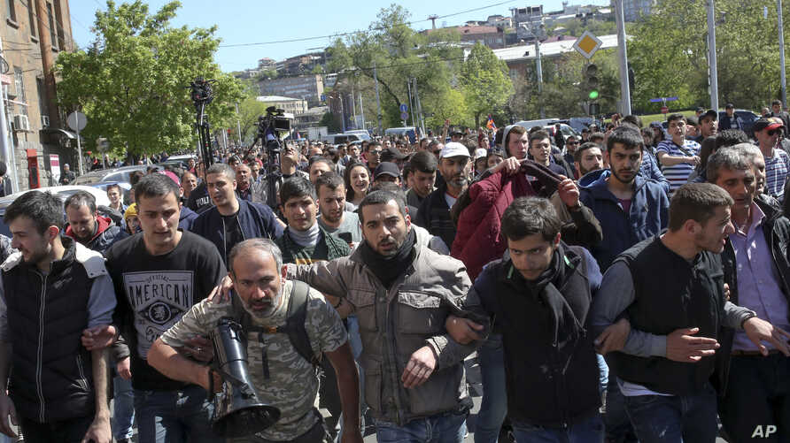 Opposition demonstrators march to protest the former president's shift into the prime minister's seat in Yerevan, Armenia, April 16, 2018. T