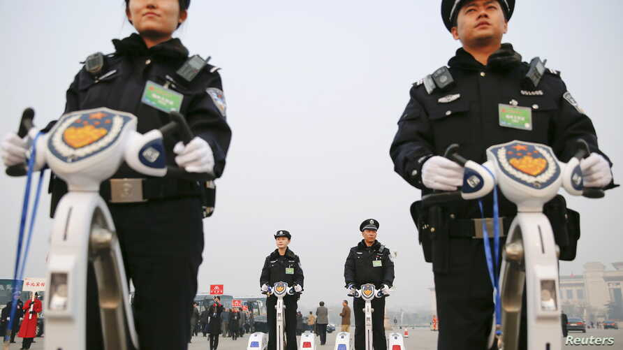 FILE - Police officers secure the area around Beijing's Great Hall of the People, March 3, 2016. Proposed changes to the country's police law would give officers more discretion over using firearms.