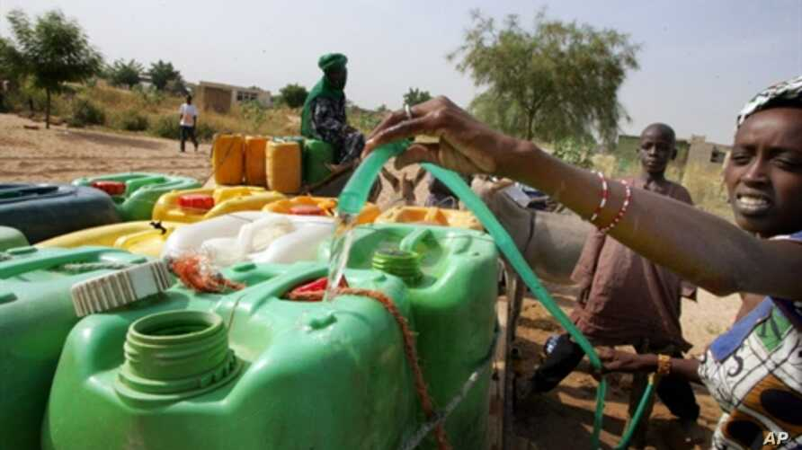 A woman fills cans of water in Touba, Senegal, 01 Nov 2007 (file photo)