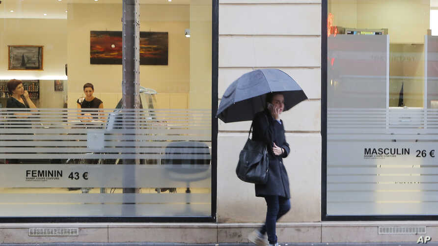 FILE - A woman is seen walking past a hair salon in Paris, Nov. 14, 2014. A Paris court on Friday acquitted a hair salon owner of homophobia in a case of an alleged gay slur she used about a homosexual employee.