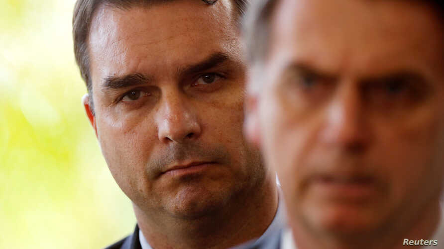 Flavio Bolsonaro, son of Brazil's President-elect Jair Bolsonaro is seen behind him at the transition government building in Brasilia, Nov. 27, 2018.