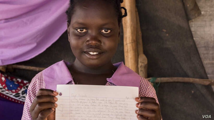 Stella Poni Vuni read a letter from Lucy, a student in Boulder, Colorado, and drew her a picture in return. She lives with her family who are refugees from South Sudan. (Carey Wagner/CARE)