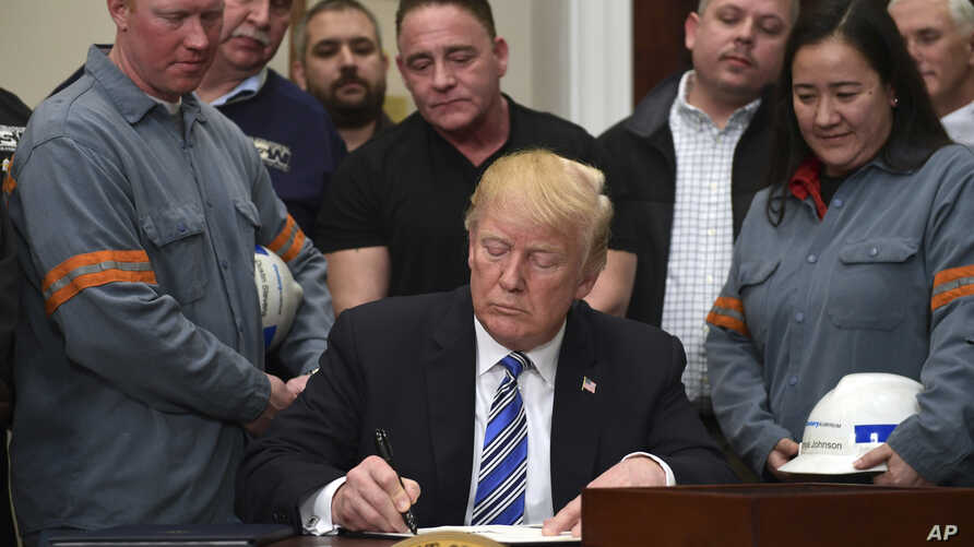 President Donald Trump signs a proclamation on steel imports during an event in the Roosevelt Room of the White House in Washington, March 8, 2018. He also signed one for aluminum.