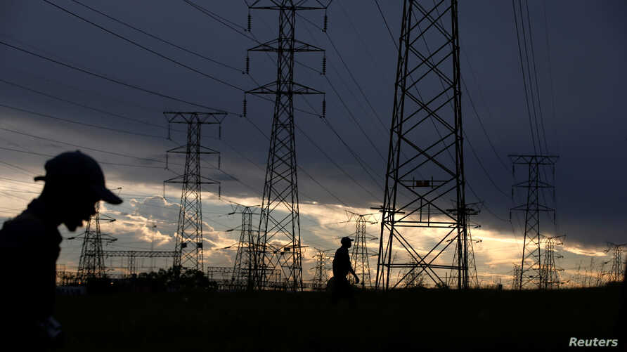 FILE - Men walk past electricity pylons as they return from work in Orlando, Soweto township, South Africa, March 18, 2019.