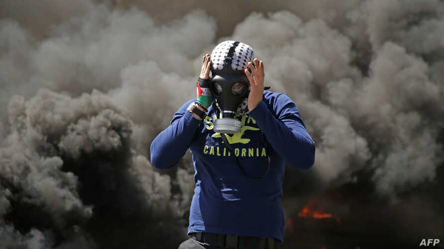 A Palestinian man wears a gas mask next to burning tires during a protest in the West Bank city of Ramallah.