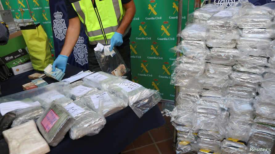Police display a portion of the six tons of cocaine, money and other material which was seized during a drug bust at an industrial estate at the police headquarters in Malaga, Spain, Oct. 25, 2018.