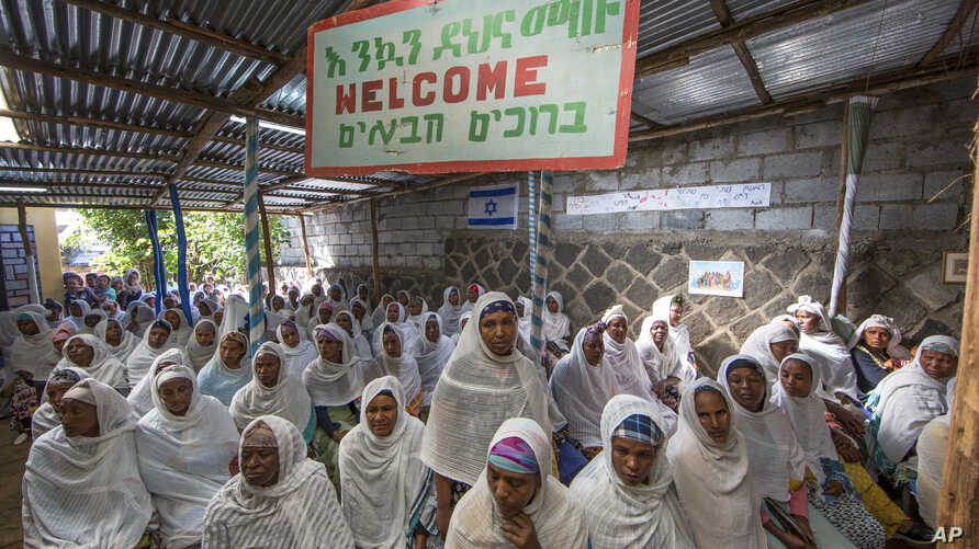 """Members of Ethiopia's Jewish community gather below a banner reading """"Welcome"""" in Amharic, English and Hebrew, to protest the Israeli government's decision not to allow all of them to emigrate to Israel, leaving their families divided between the two"""