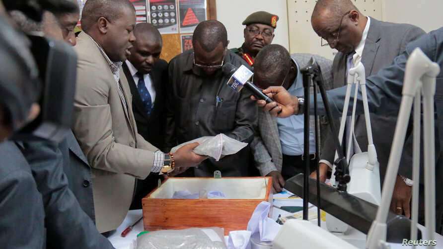 Tanzanian Minister for Finance and Planning Philip Mpango, center, and other government officials look at diamonds seized at the airport in Dar es Salaam, Tanzania, Sept. 9, 2017.