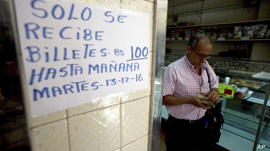 "A man counts his 100-bolivar notes next to a sign alerting customers with a message in Spanish that reads: ""100-bolivar notes will only be received until Tuesday, 12-13-16,"" inside a bakery in downtown Caracas, Venezuela, Dec. 12, 2016."