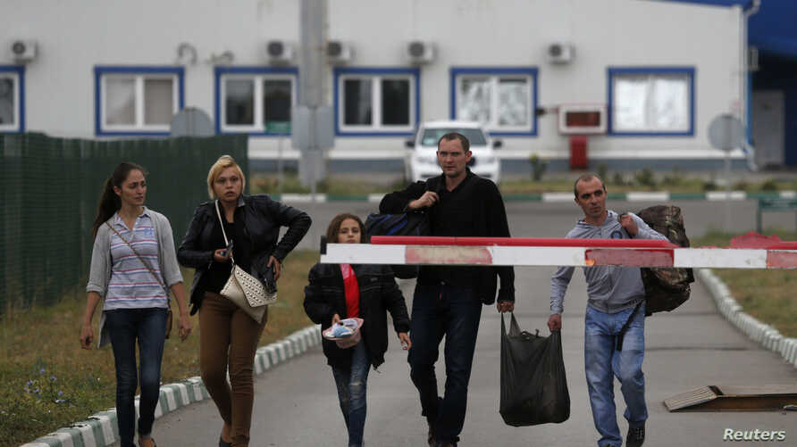 Ukrainian refugees walk from Ukraine into Russia at a border crossing point in Russia's Rostov Region, Aug. 19, 2014.