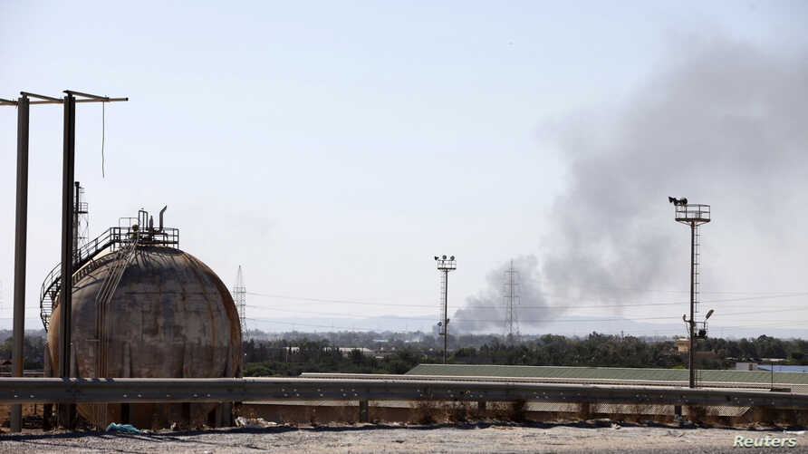 Smoke rises near oil tanks after heavy fighting between rival militias broke out near the airport in Tripoli, July 23, 2014.