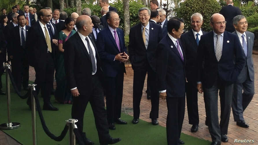 Delegates of the G20 Finance Ministers and Central Bank Governors Meeting talk as they arrive for an official photograph in the northern Australian city of Cairns, Sept. 20, 2014.