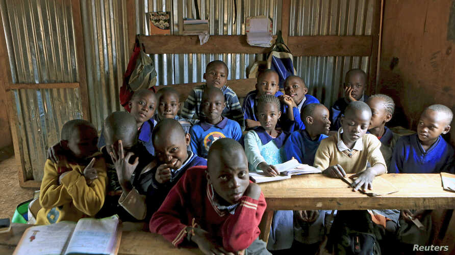 FILE - A class of children between the ages of six and seven years old pose for pictures in their classroom at Gifted Hands Educational Center in Kenya's Kibera neighborhood in the capital Nairobi, September 2015.