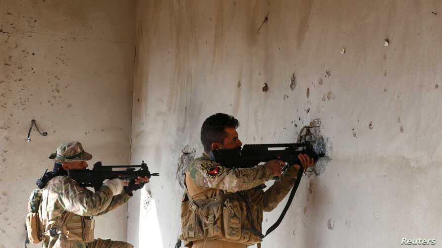 Iraqi security forces take cover during clashes with Islamic State militants, north of Mosul, Iraq, Dec. 30, 2016.