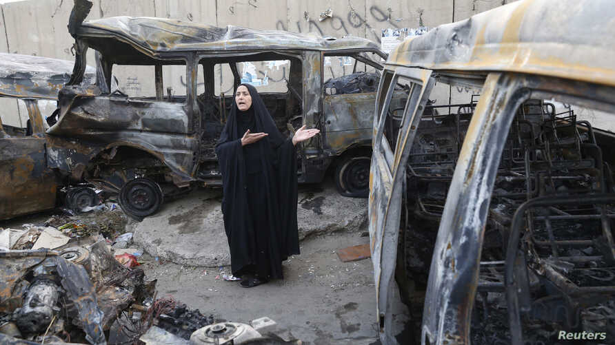 A woman gestures next to vehicles destroyed in a car bomb attack in the Shaoula neighbourhood of Baghdad, Oct. 12, 2014.