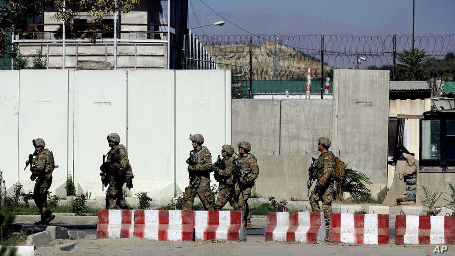 U.S. military forces stand guard at the site of a suicide attack near a U.S. military camp in Kabul, Afghanistan, Sept. 16, 2014.