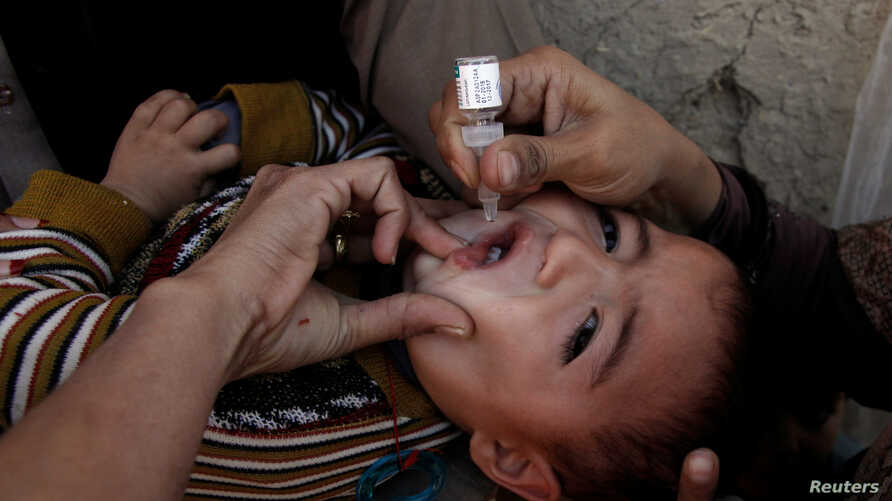 A boy receives polio vaccine drops by anti-polio vaccination workers along a street in Quetta, Pakistan, Jan. 2, 2017.