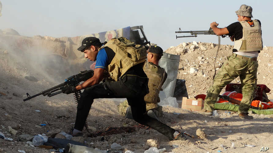 FILE - Iraqi security forces defend their positions against an Islamic State group attack in Husaybah, 8 kilometers (5 miles) east of Ramadi, Iraq, June 15, 2015.