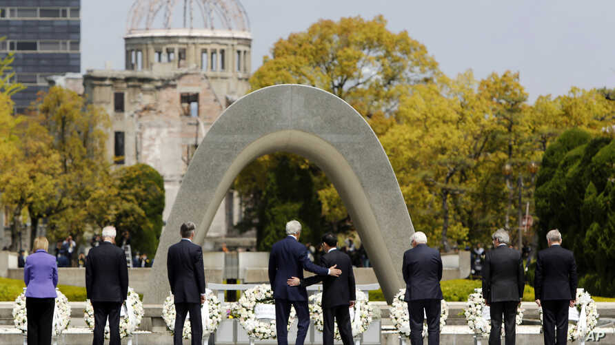 U.S. Secretary of State John Kerry, center left, puts his arm around Japan's Foreign Minister Fumio Kishida, center right, after they and fellow G7 foreign ministers laid wreaths at the cenotaph at Hiroshima Peace Memorial Park in Hiroshima, western ...