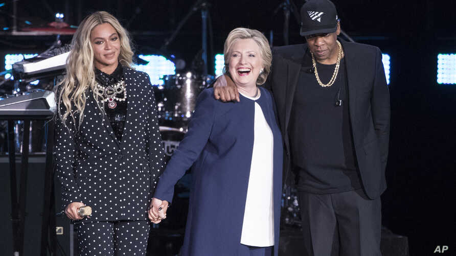 Jay Z, right, and Beyonce, left, stand with Democratic presidential candidate Hillary Clinton during a campaign rally in Cleveland, Nov. 4, 2016.