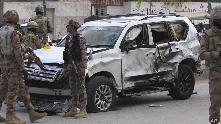 Pakistan paramilitary troops gather next to a damaged vehicle at the site of a suicide bombing in Quetta, Pakistan, Saturday, Nov. 25, 2017.