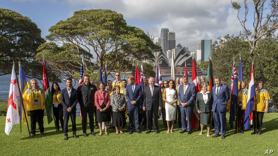 Britain's Prince Harry, center, and his wife Meghan, the Duchess of Sussex, center right, meet the Australian Governor-General Sir Peter Cosgrove and Lady Cosgrove, and representatives of Invictus Games participating countries in Sydney, Tuesday, Oct
