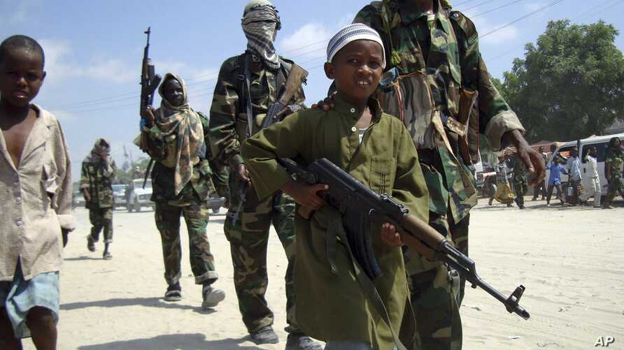 FILE - A young boy leads hard-line Islamist al-Shabab fighters as they conduct military exercises in northern Mogadishu's Suqaholaha neighborhood, Somalia.