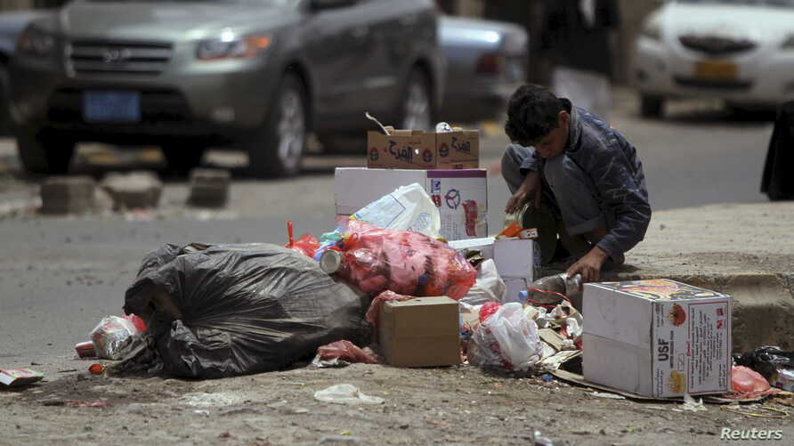 A boy searches for food amongst litter on a street in Sana'a, Yemen, April 8, 2015.