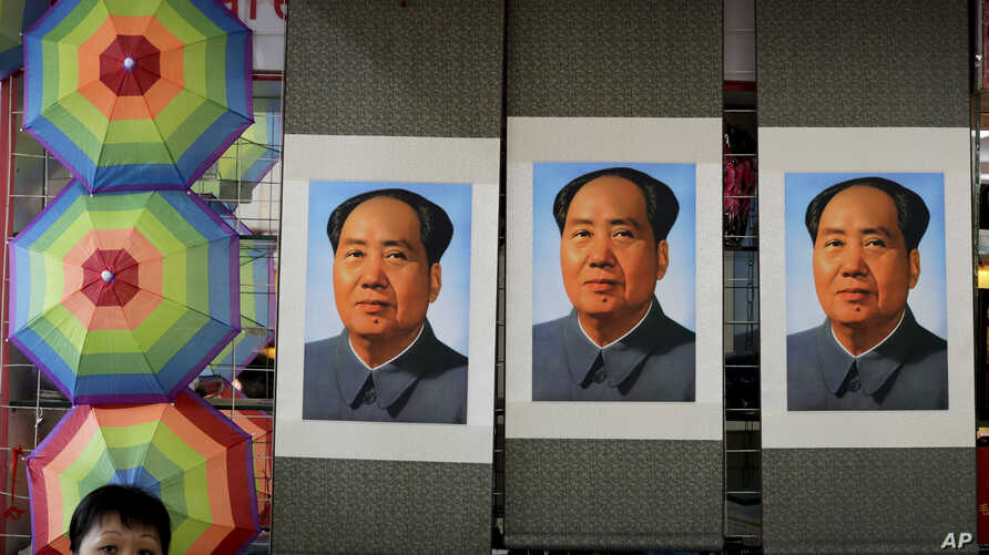 A salesperson sits near posters of the late communist leader Mao Zedong on display for sale at a shop near Tiananmen Square in Beijing, Sept. 9, 2016.