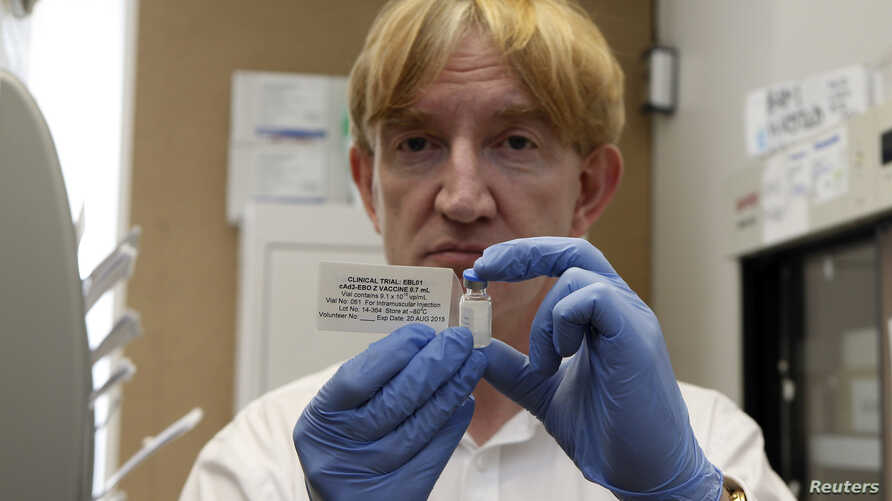 FILE - Professor Adrian Hill, director of the Jenner Institute and chief investigator of the trials, holds a phial containing the Ebola vaccine at the Oxford Vaccine Group Centre for Clinical Vaccinology and Tropical Medicine (CCVTM) in Oxford, south