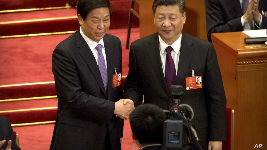 FILE - Chinese President Xi Jinping, right, poses with Li Zhanshu, March 17, 2018, after Li was elected the new chairman of China's National People's Congress (NPC) during a plenary session of the NPC in Beijing. Xi will not attend celebrations of th