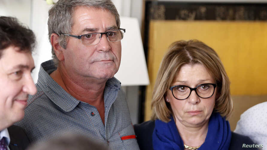 Pascal Fauret (C), one of the two French pilots who had been in the Dominican Republic awaiting a court appeal of their conviction for drug trafficking and now back in France, attends a news conference with his wife Sabine Fauret (R) at his lawyer's