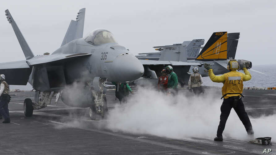 FILE - A flight deck director signals a fighter jet to move on the deck of the nuclear-powered aircraft carrier the USS John C. Stennis, June 15, 2016.