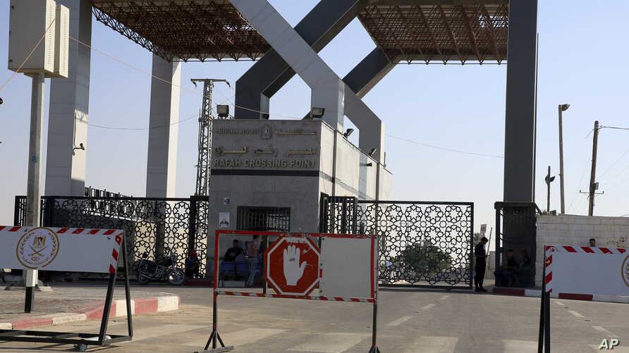 Palestinian security officers and residents sit at the closed entrance of the Rafah border crossing with Egypt southern Gaza Strip, July 17, 2018. The border was closed Sunday as Egyptian mediators work to broker a cease-fire.