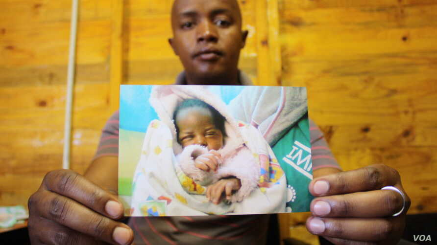 Brown Lekekela, a community leader and counselor in the Johannesburg settlement of Diepsloot, holds the photograph of a baby he helped rescue from neglect and abuse.