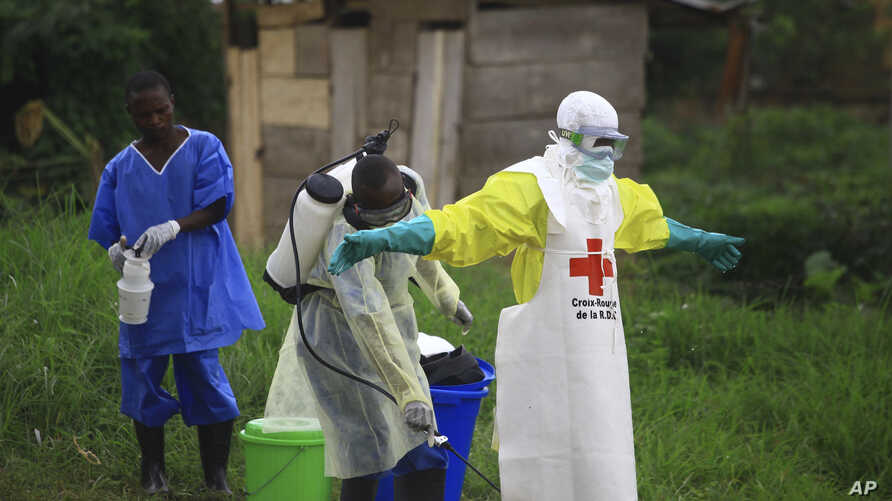 FILE - A  health worker sprays disinfectant on his colleague after working at an Ebola treatment centre in Beni, Eastern Congo.