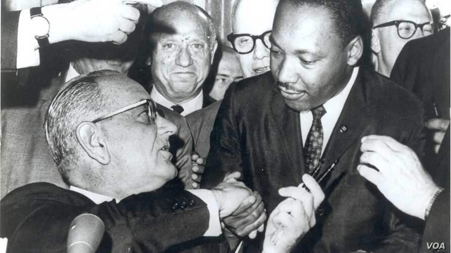 Photograph of President Lyndon Johnson signing the Voting Rights Act as Martin Luther King, Jr., with other civil rights leaders in the Capitol Rotunda, Washington, DC, August 6, 1965. Creative Commons