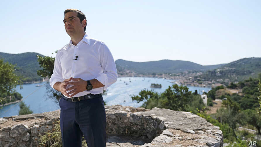 In this photo released by Greek Prime Minister's office, Greek Prime Minister Alexis Tsipras delivers a speech from the western Greek island of Ithaca, legendary home of the ancient mariner Odysseus, hero of Homer's Odyssey epic, on Aug. 21, 2018.