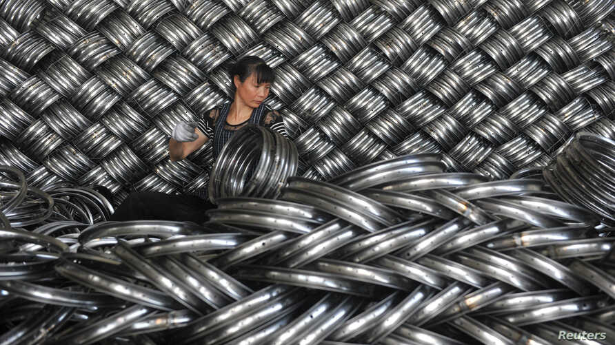 FILE - A woman works on packaging bicycle rim steels for export at a workshop of a company manufacturing sports equipment in Hangzhou, Zhejiang province, China, June 4, 2018.