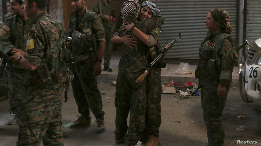 Syria Democratic Forces (SDF) female fighters embrace each other in the city of Manbij, in Aleppo Governorate, Syria, Aug.10, 2016.
