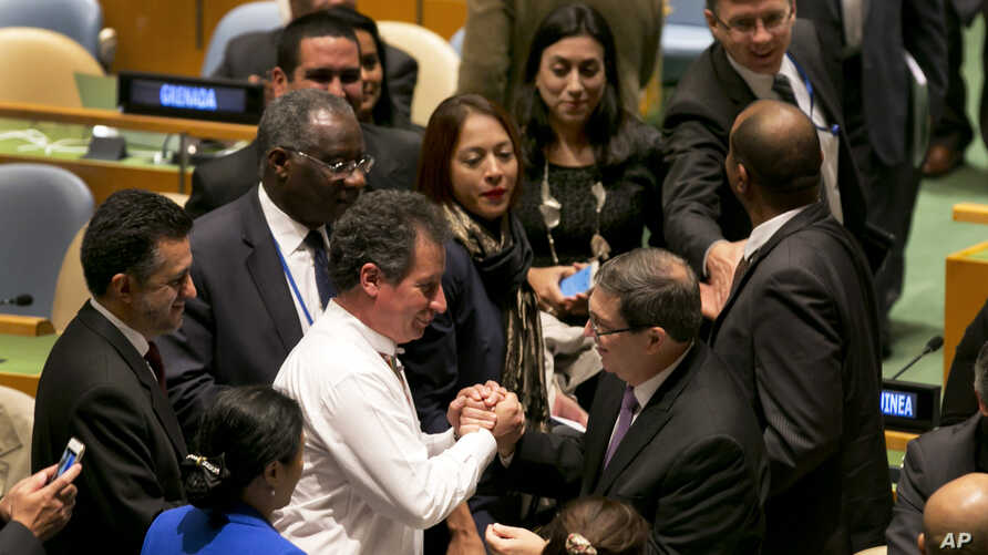Cuba's Foreign Minister Bruno Rodriguez, center right, is congratulated by fellow U.N. delegates after a vote on the annual draft resolution calling for an end to the U.S.-led five-decade embargo against the Caribbean nation, in the United Nations Ge